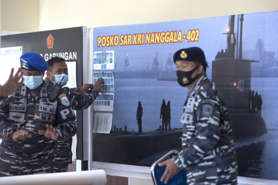 A member of Indonesian military officials sets the pictures of Indonesian Navy submarine KRI Nanggala that went missing while participating in a training exercise on Wednesday, at a command at Ngurah Rai Airport, Bali, Indonesia on Friday, April 23, 2021. Rescuers continued an urgent search Friday for an Indonesian submarine that disappeared two days ago and has less than a day's supply of oxygen left for its crew.(AP Photo/Firdia Lisnawati)