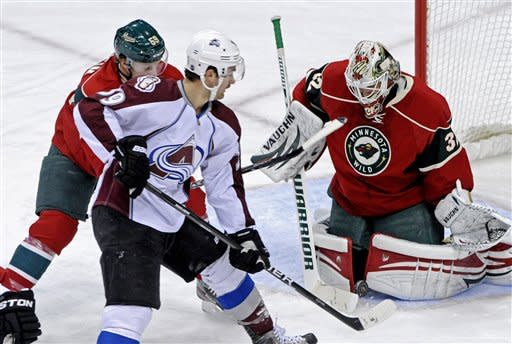 Minnesota Wild's Kris Fredheim, left, defends against Colorado Avalanche's T.J. Galiardi, center, as Wild goalie Niklas Backstrom, right, of Finland, stops a shot in the first period of an NHL hockey game Thursday, Nov. 17, 2011, in St. Paul, Minn. (AP Photo/Jim Mone)