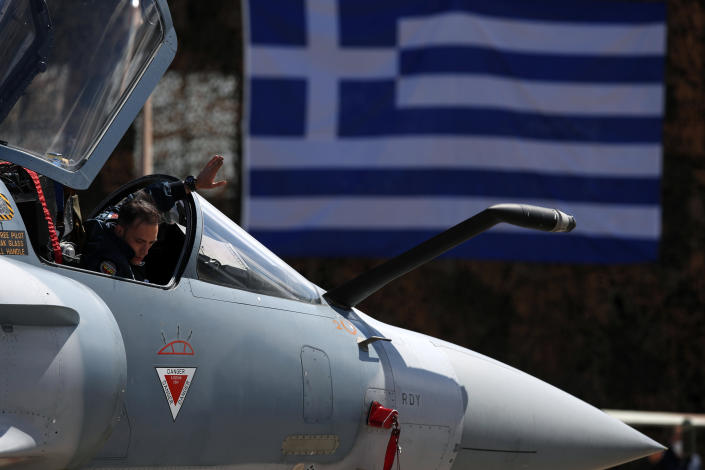 A Greek pilot of a Mirage 2000-5 gives directions to a ground crew member at Andravida air base, about 279 kilometres (174 miles) southwest of Athens, Tuesday, April 20, 2021. Greece vowed Tuesday to expand military cooperation with traditional NATO allies as well as Middle Eastern powers in a race to modernize its armed forces and face its militarily assertive neighbor Turkey. (AP Photo/Thanassis Stavrakis)
