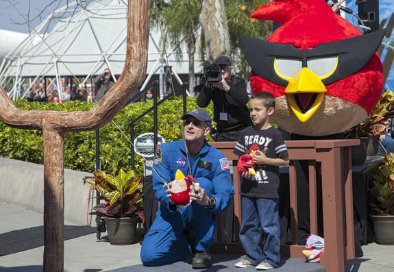 At NASA's Kennedy Space Center Visitor Complex in Florida, NASA astronaut Don Pettit uses a giant slingshot to launch a plush Angry Bird character during the grand opening of the new Angry Birds Space Encounter. Standing behind Pettit is Red Bi