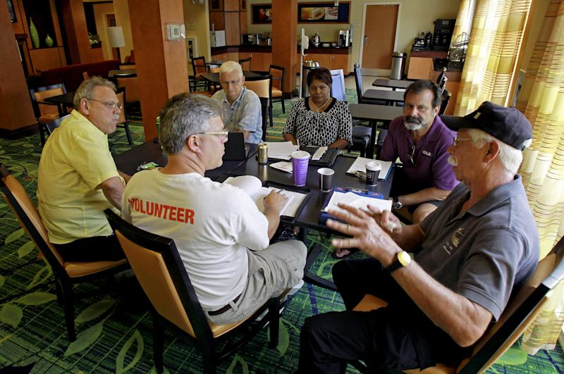 In this Wednesday, July 11, 2012 photo, Terry White, far right, leads a discussion during a business development meeting of former space workers, clockwise from center, John Hoog, Raymond Steele, Kenneth Mark Higginson Jr., Kay Sunderland and Kevin Harrington, in Titusville, Fla. (AP Photo/John Raoux)