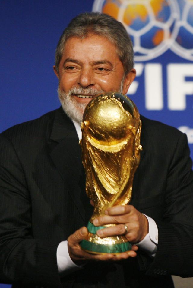FILE - In this 30 October, 2007, file photo, Brazilian President Lula holds the World Cup Trophy after it was announced that Brazil will host the 2014 Soccer World Cup in Zurich, Switzerland. Lula, the country's immensely popular and folksy former leader told the crowd at celebratory ceremony in Zurich that he would return home full of joy but also feel the burden of hosting the world's biggest sporting event. The tournament opens June 12 with Brazil facing Croatia in the opening match. (KEYSTONE/Steffen Schmidt, File)
