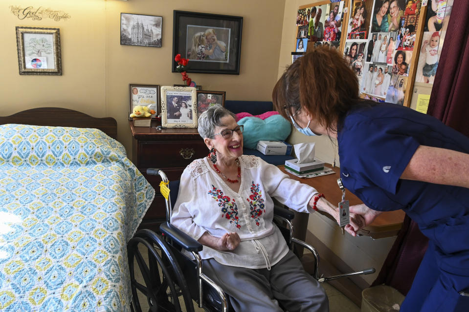 Resident Eleanor Garrison, left, talks with director of nursing Cheri Place-Chafin in her room Wednesday, Feb. 3, 2021, at Arbor Springs Health and Rehabilitation Center in Opelika, Ala. Coronavirus cases have dropped at U.S. nursing homes and other long-term care centers over the past few weeks, offering a glimmer of hope that studies and health officials link to various factors, including the start of vaccinations, the easing of a post-holiday virus surge and better prevention. (AP Photo/Julie Bennett)