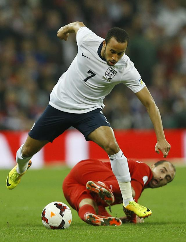 England's Andros Townsend, leaps over the lunging tackle of Poland's Adrian Mierzejewski during the World Cup Group H qualification soccer match between England and Poland at Wembley stadium in London, Tuesday, Oct. 15, 2013. (AP Photo/Kirsty Wigglesworth)