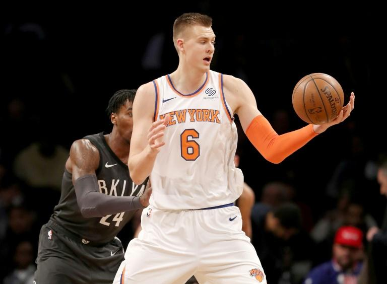 Kristaps Porzingis of the New York Knicks grabs the ball as Rondae Hollis-Jefferson of the Brooklyn Nets defends, at the Barclays Center in New York, on December 14, 2017
