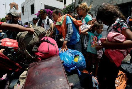 Central American migrants pick up their luggage after arriving in a caravan, as they move through Mexico toward the U.S., in Puebla, Mexico April 6, 2018. REUTERS/Henry Romero