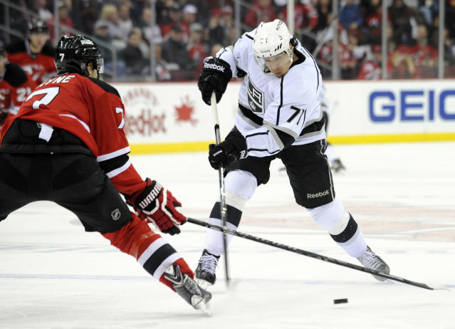 New Jersey Devils' Mark Fayne, left, pokes the puck away from Los Angeles Kings' Jordan Nolan during the first period of an NHL hockey game Friday, Nov. 15, 2013, in Newark, N.J. (AP Photo/Bill Kostroun)