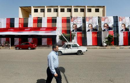 People walk in front of polling stations covered from outside by Egyptian flags and posters of Egypt's President Abdel Fattah al-Sisi during the preparations for tomorrow's presidential election in Cairo, Egypt, March 25, 2018. REUTERS/Amr Abdallah Dalsh