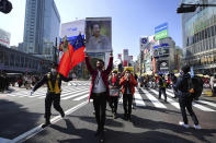 Myanmar people living in Japan and supporters march though Shibuya pedestrian crossings during a protest in Sunday, Feb. 14, 2021, in Tokyo. Thousands of people from Myanmar living in Japan marched in downtown Tokyo to protest the military coup back home. (AP Photo/Eugene Hoshiko)