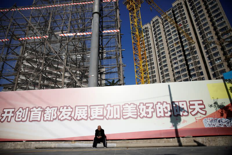 Man sits in front of a construction site in Beijing
