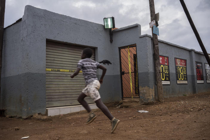 A boy runs past the tavern where the body of 5-year-old Wandi Zitho was found after he was murdered less than two weeks earlier in Orange Farm, South Africa, on April 27, 2020. The bar owner was arrested and later released because of a lack of evidence. (AP Photo/Bram Janssen)