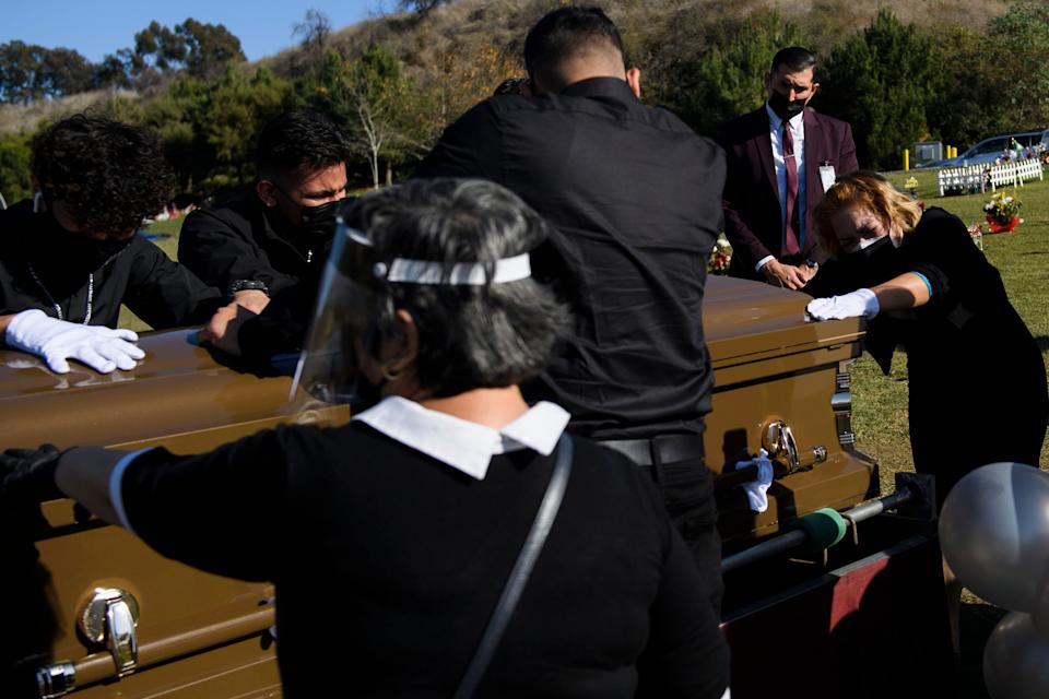 Family members mourn over the casket of Gilberto Arreguin Camacho, 58, who died from COVID-19, at a cemetery in Whittier, California, on Dec. 31. (Photo: PATRICK T. FALLON via Getty Images)