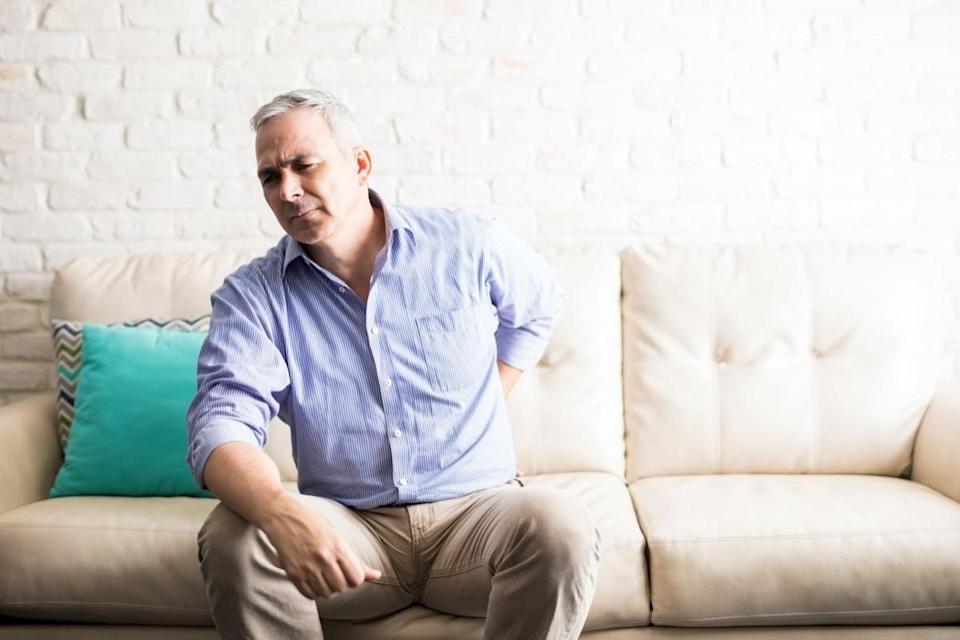 Mature man with gray hair having backache while sitting on sofa at home