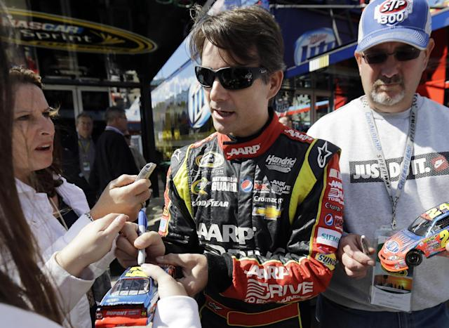 Driver Jeff Gordon signs autographs for fans as he walks to his garage during practice for Sunday's NASCAR Sprint Cup Series auto race at Chicagoland Speedway in Joliet, Ill., Friday, Sept. 13, 2013. (AP Photo/Nam Y. Huh)