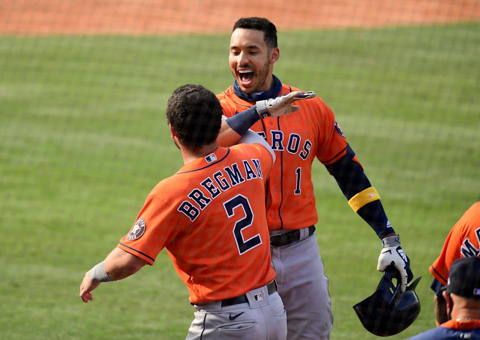 Carlos Correa is congratulated by Jose Altuve after hitting a solo home run.