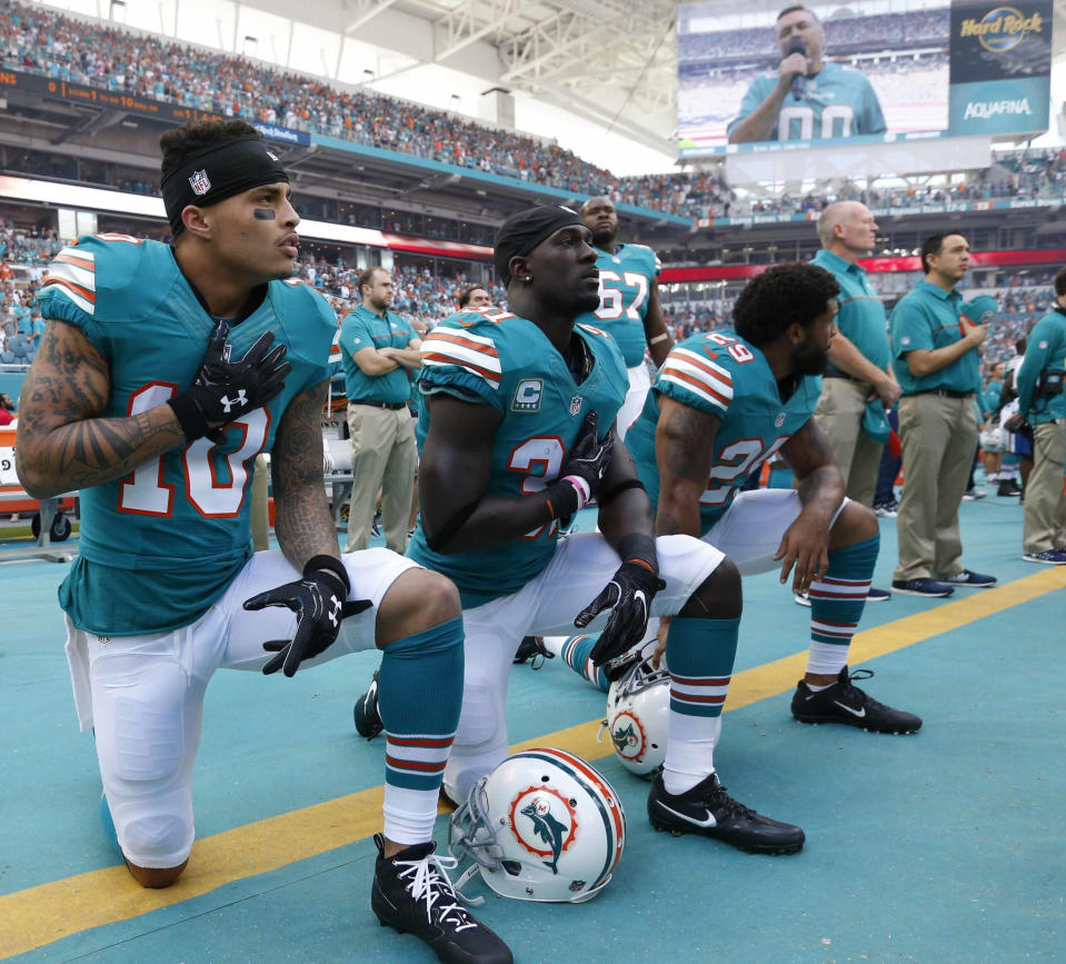 FILE - In this Sunday, Oct. 23, 2016, file photo, Miami Dolphins wide receiver Kenny Stills (10), free safety Michael Thomas (31) and defensive back Chris Culliver (29) kneel during the National Anthem before the first half of an NFL football game against the Buffalo Bills in Miami Gardens, Fla. Miami Dolphins players who protest on the field during the national anthem this season could be suspended for up to four games under a new team policy issued to players this week. The policy obtained by The Associated Press on Thursday, July 19, 2018 classifies anthem protests as conduct detrimental to the club, punishable by suspension without pay, a fine or both. (AP Photo/Wilfredo Lee, File)