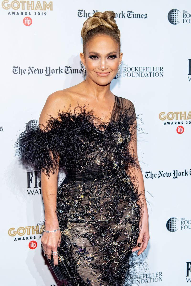 Jennifer Lopez looks stunning in a black dress with gold design and furry edges