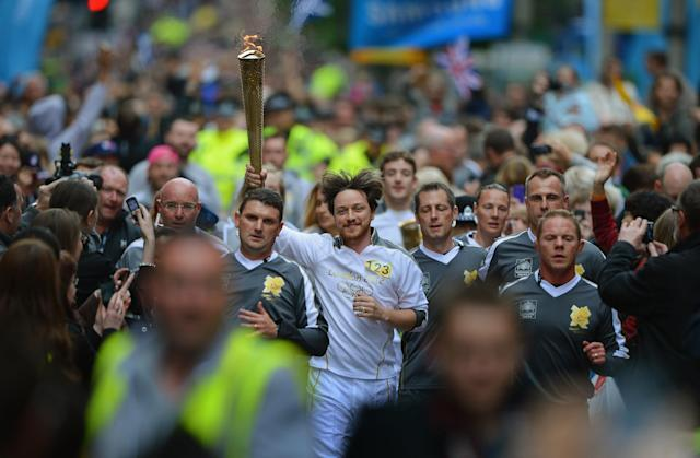 GLASGOW, SCOTLAND - JUNE 08: Actor James Mcavoy runs down Buchanan Street carrying the Olympic Torch during the leg between Stranrear and Glasgow on June 8, 2012 in Glasgow, Scotland. The Olympic torch arrived in Scotland last night to begin its tour of Scotland. The Olympic Flame is now on day 21 of a 70-day relay involving 8,000 torchbearers covering 8,000 miles. (Photo by Jeff J Mitchell/Getty Images)