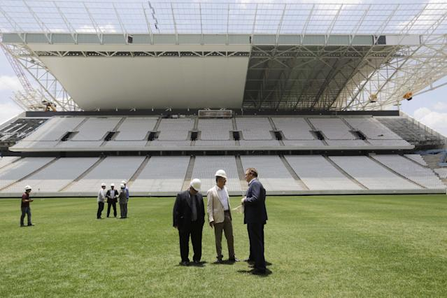FILE - In this Jan. 20, 2014 file photo, Jerome Valcke, secretary general of FIFA, right center, and Aldo Rebelo, Brazil's sports minister, center, inspect the Sao Paulo stadium, in Sao Paulo, Brazil. The stadium which hosts the opening match of the World Cup will not be finished until less than four weeks before Brazil plays Croatia on June 12. Confirming further delays Saturday, March 1, 2014, Valcke said the venue would not be ready before May 15. (AP Photo/Nelson Antoine, File)