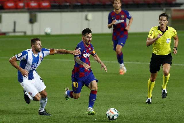 Barcelona's Lionel Messi runs for the ball next to Espanyol's David Lopez during the Spanish La Liga soccer match between FC Barcelona and RCD Espanyol at the Camp Nou stadium in Barcelona, Spain, Wednesday, July 8, 2020. (AP Photo/Joan Monfort)