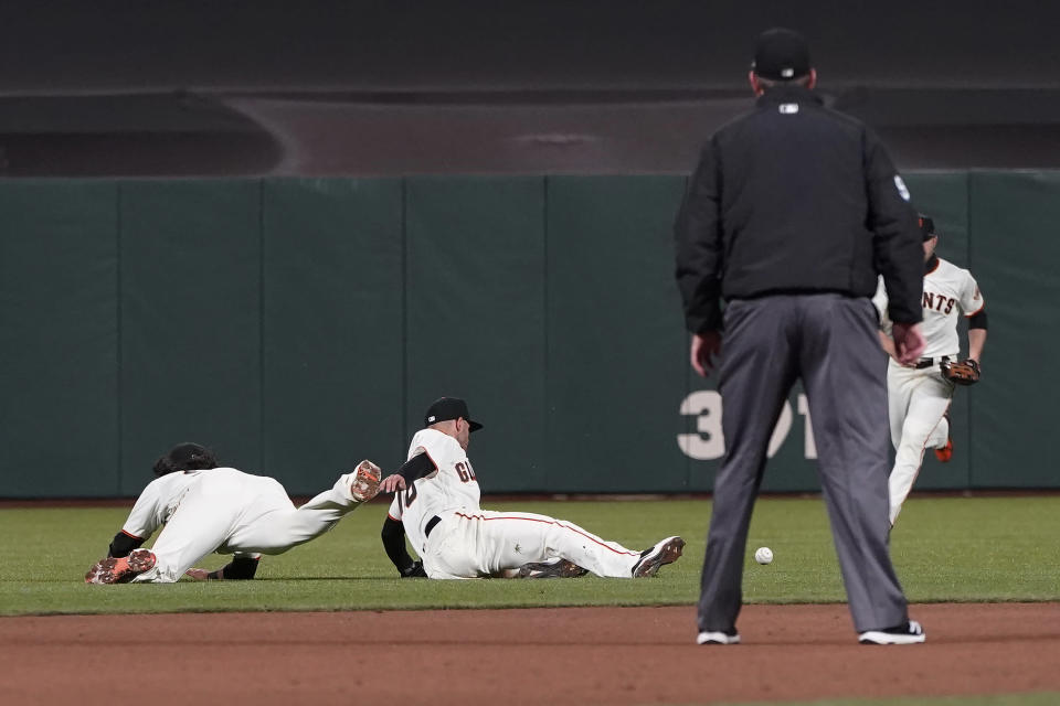 An RBI single hit by Cincinnati Reds' Alex Blandino lands near San Francisco Giants shortstop Brandon Crawford, second baseman Tommy La Stella and right fielder Austin Slater, from left, during the seventh inning of a baseball game in San Francisco, Tuesday, April 13, 2021. (AP Photo/Jeff Chiu)