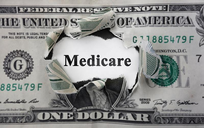"""$1 bill torn in the center with the word """"Medicare"""" showing through the hole"""