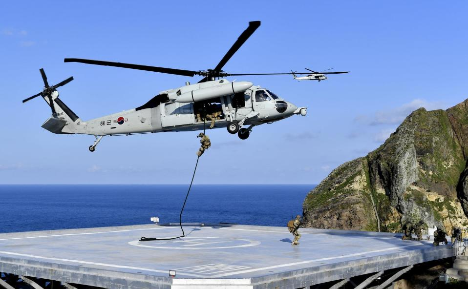 In this photo provided by South Korea's Navy, members of South Korean Navy's special forces rappel down from the UH-60 helicopter during the drill on the islets called Dokdo in Korean and Takeshima in Japanese, Sunday, Aug. 25, 2019. In a development that could possibly further complicate ties between Seoul and Tokyo, South Korea's navy on Sunday began two-day exercises on and around a group of islets controlled by South Korea but also claimed by Japan.(South Korea's Navy via AP)