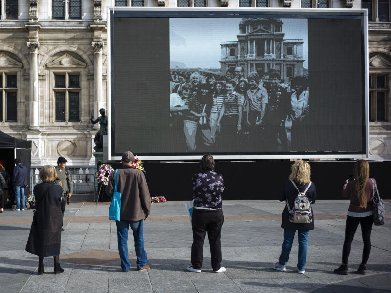 People watch former President Jacques Chirac on a giant screen set up at the Paris town hall Paris, Friday, Sept. 27, 2019. Mourners are signing memory books, flags are lowered and French politicians from across the spectrum are paying tributes to late President Jacques Chirac. (AP Photo/Kamil Zihnioglu)