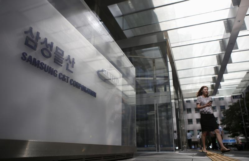 An employee walks past a logo of Samsung C&T Corp at the company's headquarters in Seoul
