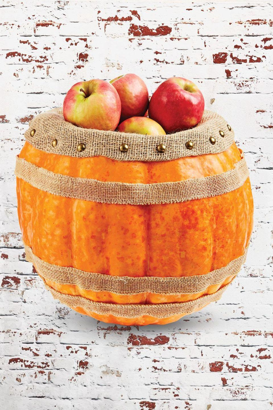 "<p>This pumpkin barrel is perfect for showing off your apple picking haul or filling with candy so that trick-or-treaters can help themselves.</p><p><strong>Make the Pumpkin Barrel:</strong> Cut off the top quarter of an extra-large pumpkin; scoop out pulp and seeds. Hot-glue three strips of ribbon around outside of pumpkin. Stuff pumpkin three-fourths full with Poly-Fil. Insert burlap fabric into the opening and fold over outside of pumpkin; hold in place with upholstery tacks. Fill with apples or desired items.</p><p><a class=""link rapid-noclick-resp"" href=""https://www.amazon.com/Afula-Burlap-BUR40-5YDS-Natural-Yards/dp/B07B9KLKXG/ref=sr_1_1_sspa?tag=syn-yahoo-20&ascsubtag=%5Bartid%7C10050.g.279%5Bsrc%7Cyahoo-us"" rel=""nofollow noopener"" target=""_blank"" data-ylk=""slk:Shop Burlap"">Shop Burlap</a><br></p>"