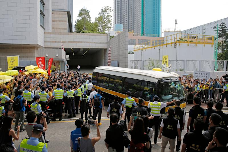 Supporters gather around a prison van carrying Occupy Central leaders Chan Kin-man, Benny Tai, Raphael Wong and Shiu Ka-chun outside a court in Hong Kong (Kin Cheung/AP)