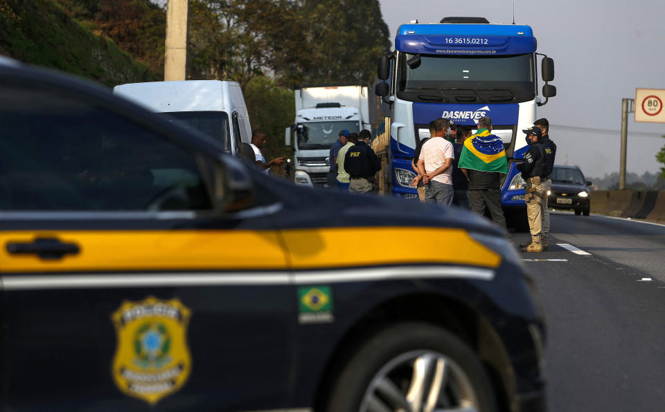 A police vehicle is seen near truck drivers blocking the Regis Bittencourt road, 30 kilometres south of Sao Paulo, Brazil, during a demo in support of President Jair Bolsonaro, on September 9, 2021. - Truck drivers blocked highways across Brazil Thursday in support of President Jair Bolsonaro, who has sought to fire up his far-right base as he fights sinking poll numbers and a supposedly hostile political establishment. The truckers launched their protest Tuesday on Brazilian Independence Day, when Bolsonaro held massive demonstrations to rally his base against what he calls attacks by the Supreme Court and electoral authorities. (Photo by Miguel SCHINCARIOL / AFP) (Photo by MIGUEL SCHINCARIOL/AFP via Getty Images)