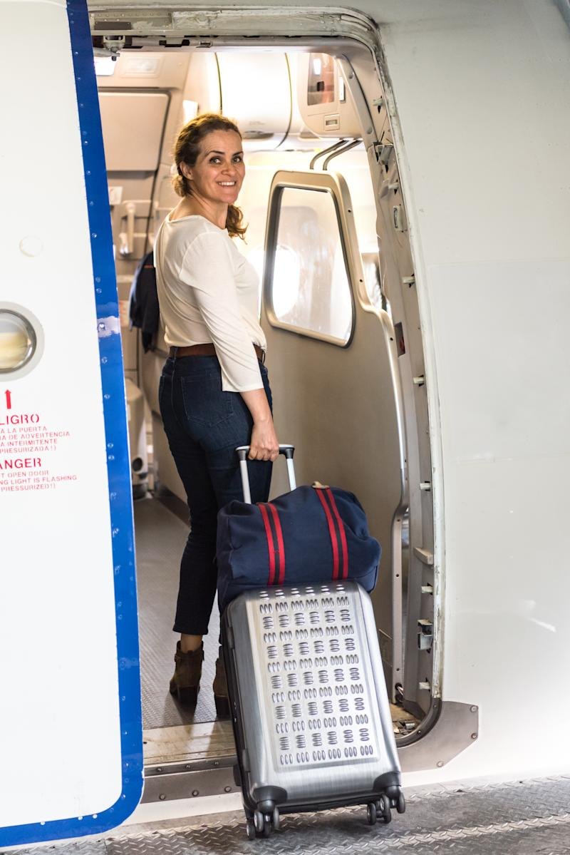 Smiling mature woman boarding an airplane carrying her carry on luggage
