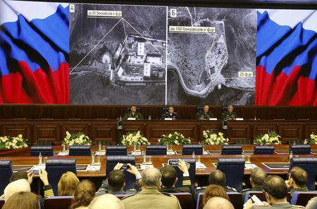 Defence ministry officials sit under screens with satellite images on display during a briefing in Moscow