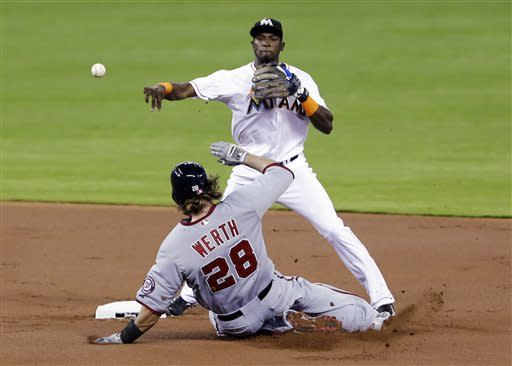 Miami Marlins shortstop Adeiny Hechavarria throws to first base to complete the double play as Washington Nationals' Jayson Werth slides into second base during the first inning of a baseball game, Tuesday, April 16, 2013, in Miami. Roger Bernadina was out at first base. (AP Photo/Wilfredo Lee)