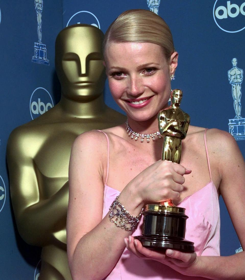 """Gwyneth Paltrow poses backstage with her best actress Oscar for her role in """"Shakespeare in Love,"""" at the 71st Annual Academy Awards at the Dorothy Chandler Pavilion of the Los Angeles Music Center Sunday, March 21, 1999. (AP Photo/Reed Saxon)"""