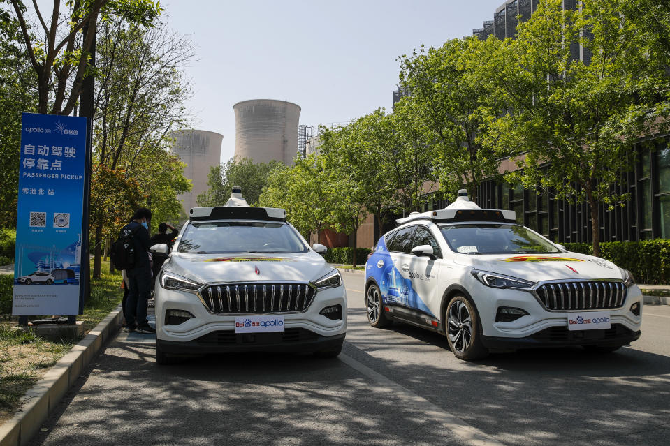 Baidu Apollo Robotaxis pass by a passenger pickup point setup at the Shougang Park in Beijing, Sunday, May 2, 2021. Chinese tech giant Baidu rolled out its paid driverless taxi service on Sunday, making it the first company that commercialized autonomous driving operations in China. (AP Photo/Andy Wong)