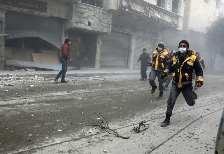 Syrian rescuers and civilians running from the site of a Syrian government bombardment in Hamouria last week, in the Eastern Ghouta region just outside Damascus