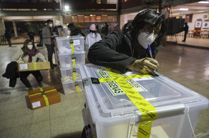A poll worker validates a ballot box at the end of the first day the Constitutional Convention election to select assembly members that will draft a new constitution, in Santiago, Chile, Saturday, May 15, 2021. The face of a new Chile begins taking shape this weekend as the South American country elects 155 people to draft a constitution to replace one that has governed it since being imposed during a military dictatorship. (AP Photo/Esteban Felix)