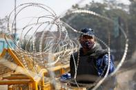 A member of the Rapid Action Force (RAF), wearing a protective face mask, is seen through barbed wire at the site of a protest against the newly passed farm bills at Singhu border near Delhi