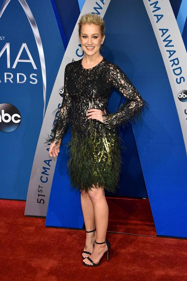 <p>The singer kept things flirty with a lace and sequin black dress. She made the piece even flashier with green feathers on the hemline. (Photo: Getty Images) </p>