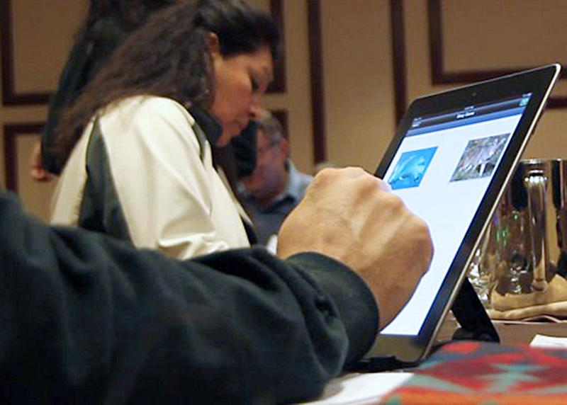 Lynette St. Clair, rear, of the Eastern Shoshone Tribe, participates in a language-learning app workshop in Las Vegas in this photo made on Dec. 8, 2011.  The workshop, organized by software company Thornton Media, trains tribal members to use smartphone and tablet apps as part of efforts to revitalize languages that are on the brink of extinction. (AP Photo/Kara Thornton)