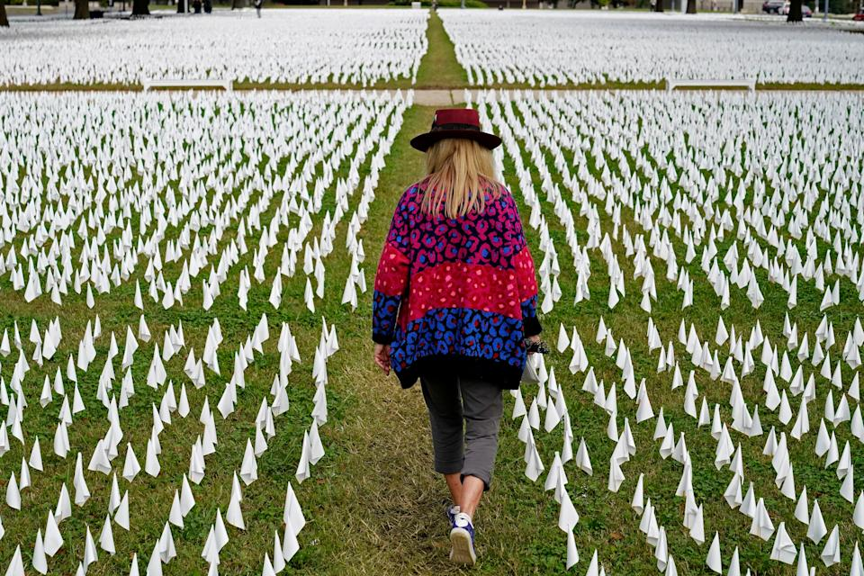 Artist Suzanne Brennan Firstenberg walks among thousands of white flags planted in remembrance of Americans who have died of Covid-19 near Robert F. Kennedy Memorial Stadium in WashingtonAP