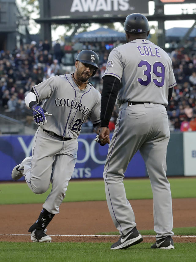 Colorado Rockies' Ian Desmond, left, is congratulated by third base coach Stu Cole (39) after hitting a solo home run against the San Francisco Giants during the fourth inning of a baseball game in San Francisco, Tuesday, June 25, 2019. (AP Photo/Jeff Chiu)