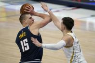 Denver Nuggets center Nikola Jokic (15) attempts to pass the ball as Dallas Mavericks guard Luka Doncic, right, defends in the second half of an NBA basketball game in Dallas, Monday, Jan. 25, 2021. (AP Photo/Tony Gutierrez)