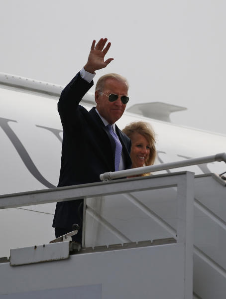 U.S. Vice President Joe Biden accompanied by his wife Jill, waves upon his arrival at the airport in New Delhi, India, Monday, July 22, 2013. Biden arrived in India Monday on a four day visit aimed at boosting trade and strengthening strategic relations as Washington pursues its new Asia-Pacific policy. (AP Photo/ Saurabh Das)