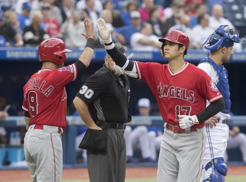 Los Angeles Angels' Shohei Ohtani (17) is greeted by teammate Tommy La Stella after hitting a three-run home run against the Toronto Blue Jays during second-inning baseball game action in Toronto, Monday, June 17, 2019. (Fred Thornhill/The Canadian Press via AP)
