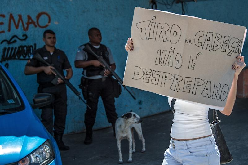 """A woman holds a poster arguing a shoot in the head is not a mistake, during the """"march for peace"""" at Rio de Janeiro's Alemao favela on April 4, 2015 to protest the death of a ten-year-old boy, shot dead by the police (AFP Photo/Christophe Simon)"""