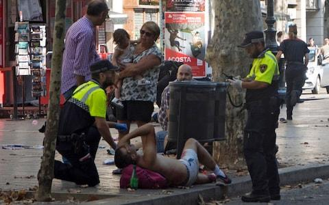 Police officers help the injured after the van crashed into pedestrians in Las Ramblas - Credit: David Armengou/EPA