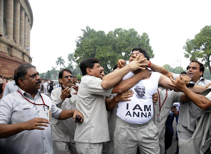 "Security personnel detain a supporter of India's anti-corruption activist Anna Hazare outside the Indian parliament in  New Delhi, India, Friday, Aug. 26, 2011. Rahul Gandhi, the scion of India's most powerful political family praised a reform activist for galvanizing anger against corruption but said Friday that using a hunger strike to force lawmakers to adopt an anti-corruption bill set ""a dangerous precedent for a democracy."" (AP Photo)"